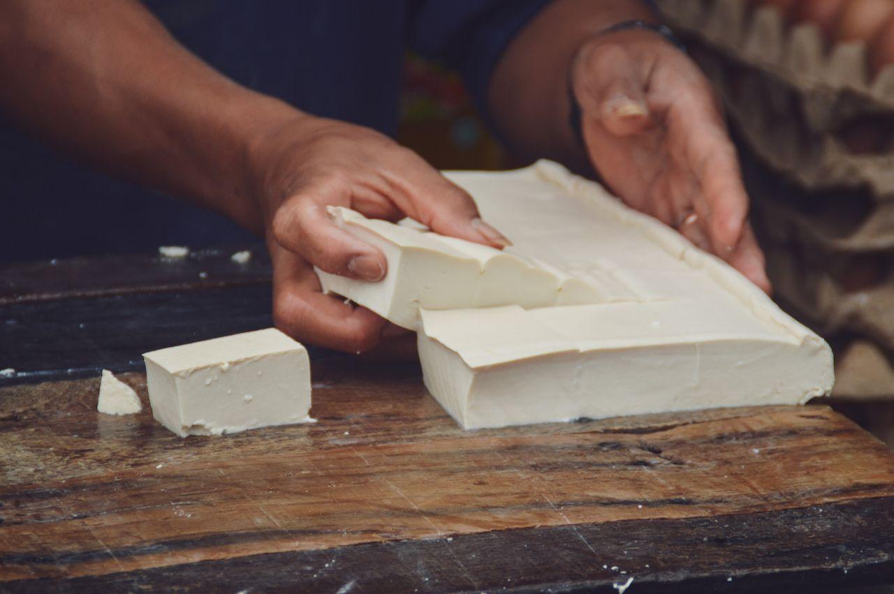 block of tofu being cut