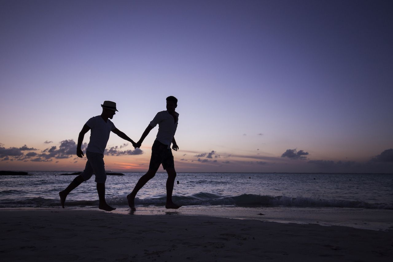 two men running on the beach holding hands, at sunset. Isla Mujeres, Mexico