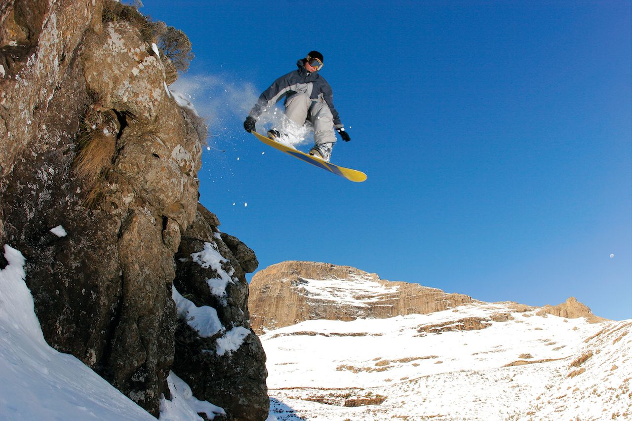 A snowboarder jumps off a cliff in rural Lesotho