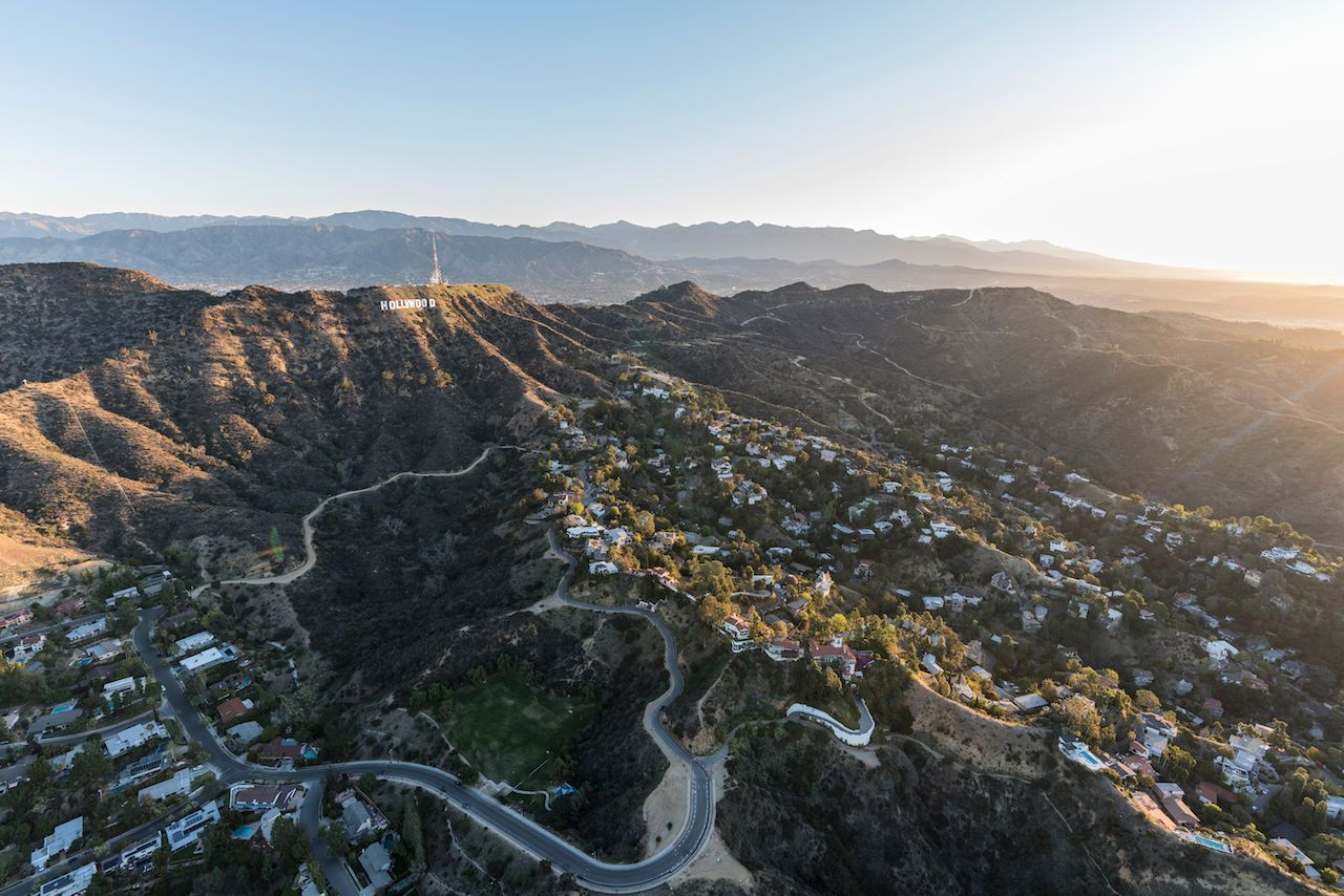 Aerial morning view of Hollywood Sign above hillside homes in LA