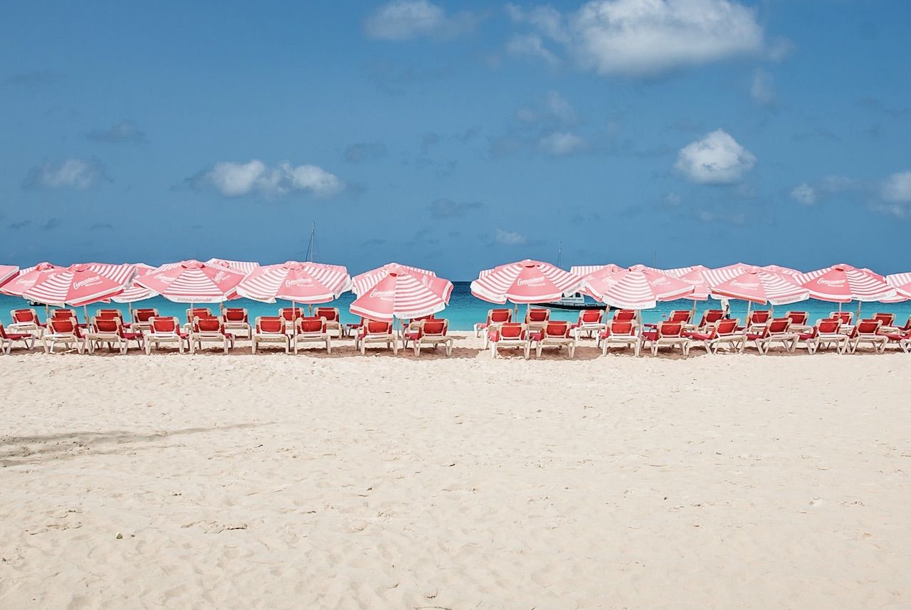 Departure Beach lounge with red beach chairs and pink umbrellas in Barbados