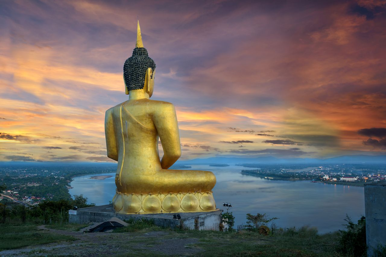 Big buddha over the city on river in twilight in Laos