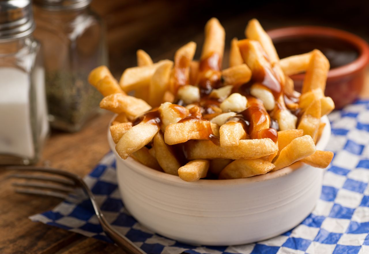 Bowl of Canadian poutine, fries topped with gravy and cheese curds