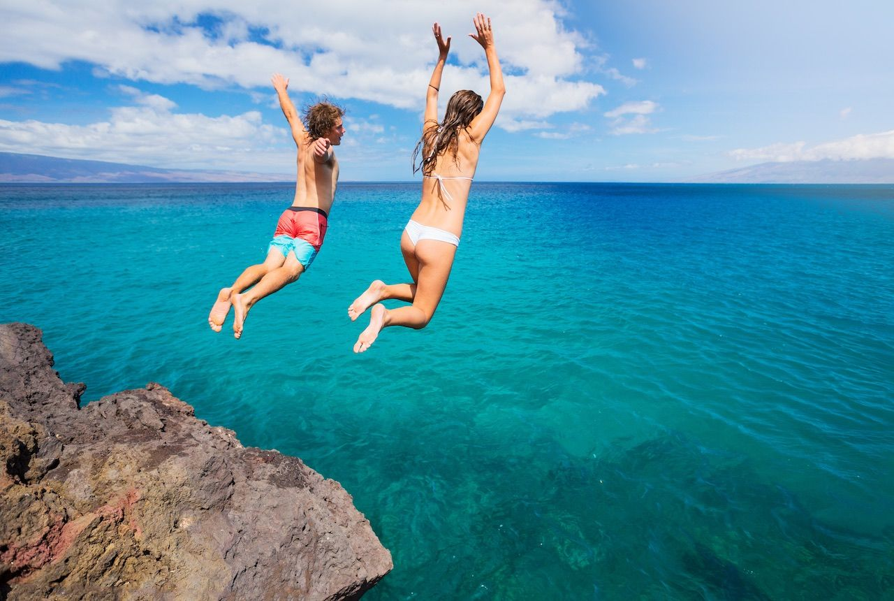 Couple jumping off a cliff ocean