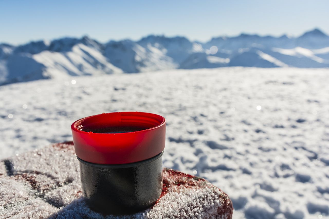 Cup of hot tea on a table with a boundary marker in the winter in the mountains