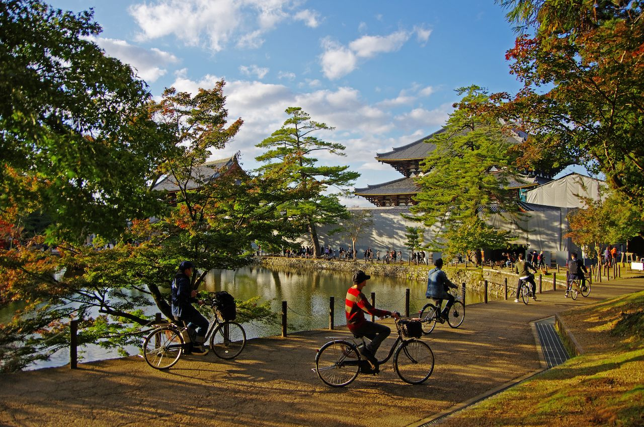 Cyclists at the Todai-ji Temple in Japan under blue skies