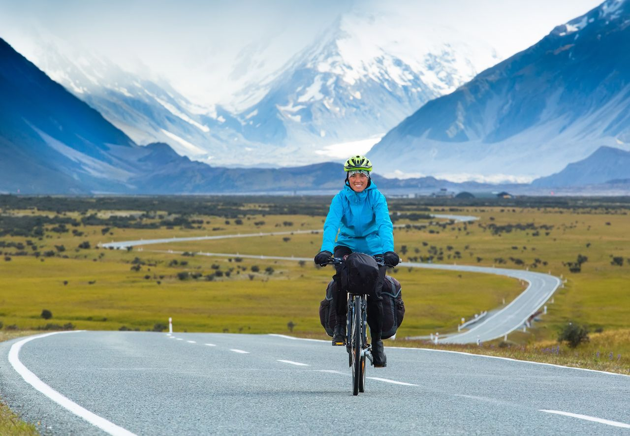Cyclists winds along a road with snowy mountains to her back in New Zealand