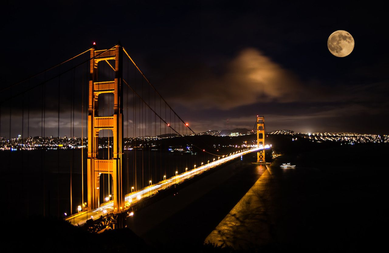 Golden Gate bridge at night with full moon shining on San Francisco skyline