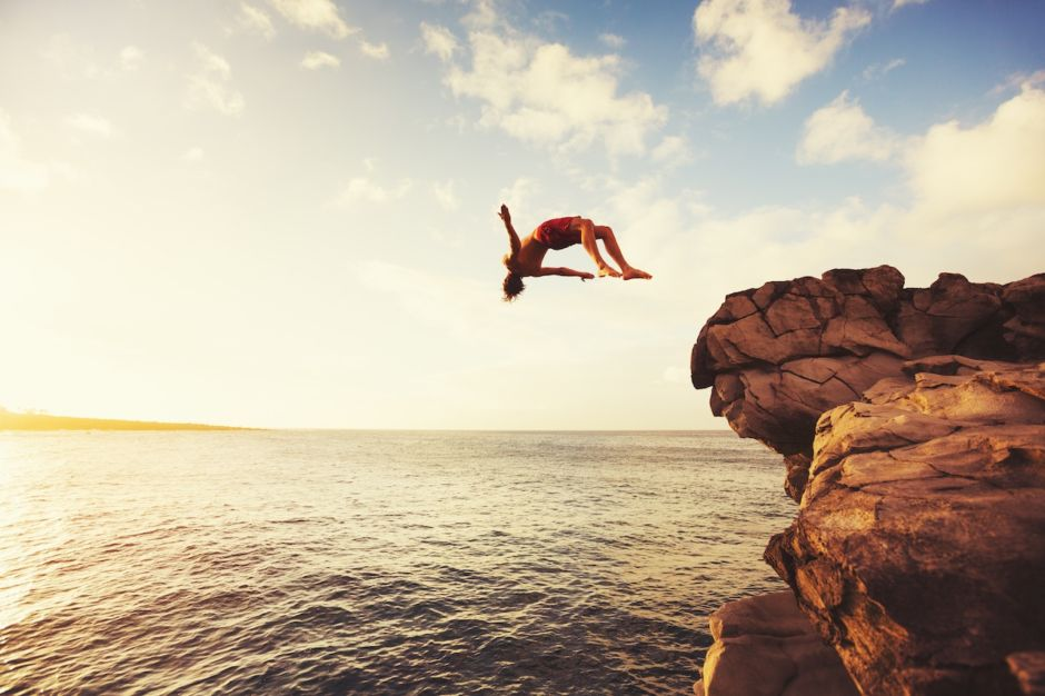 Man jumping from a cliff into the ocean