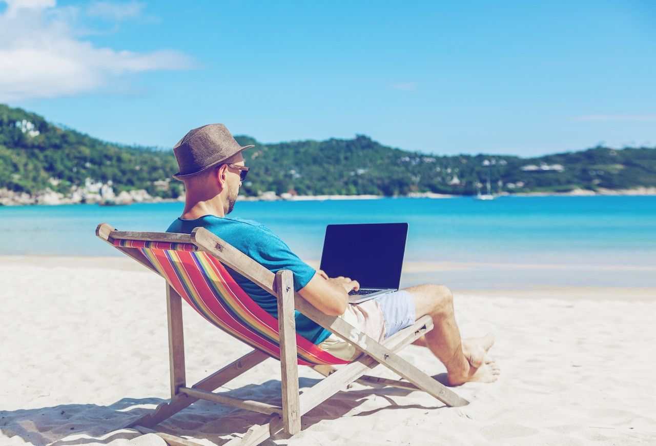 Man with a laptop at the beach