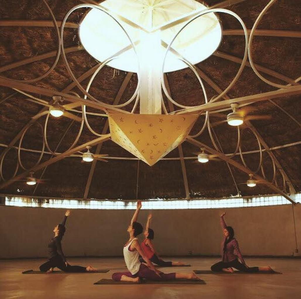 women doing yoga in a yurt under an artistic light fixture