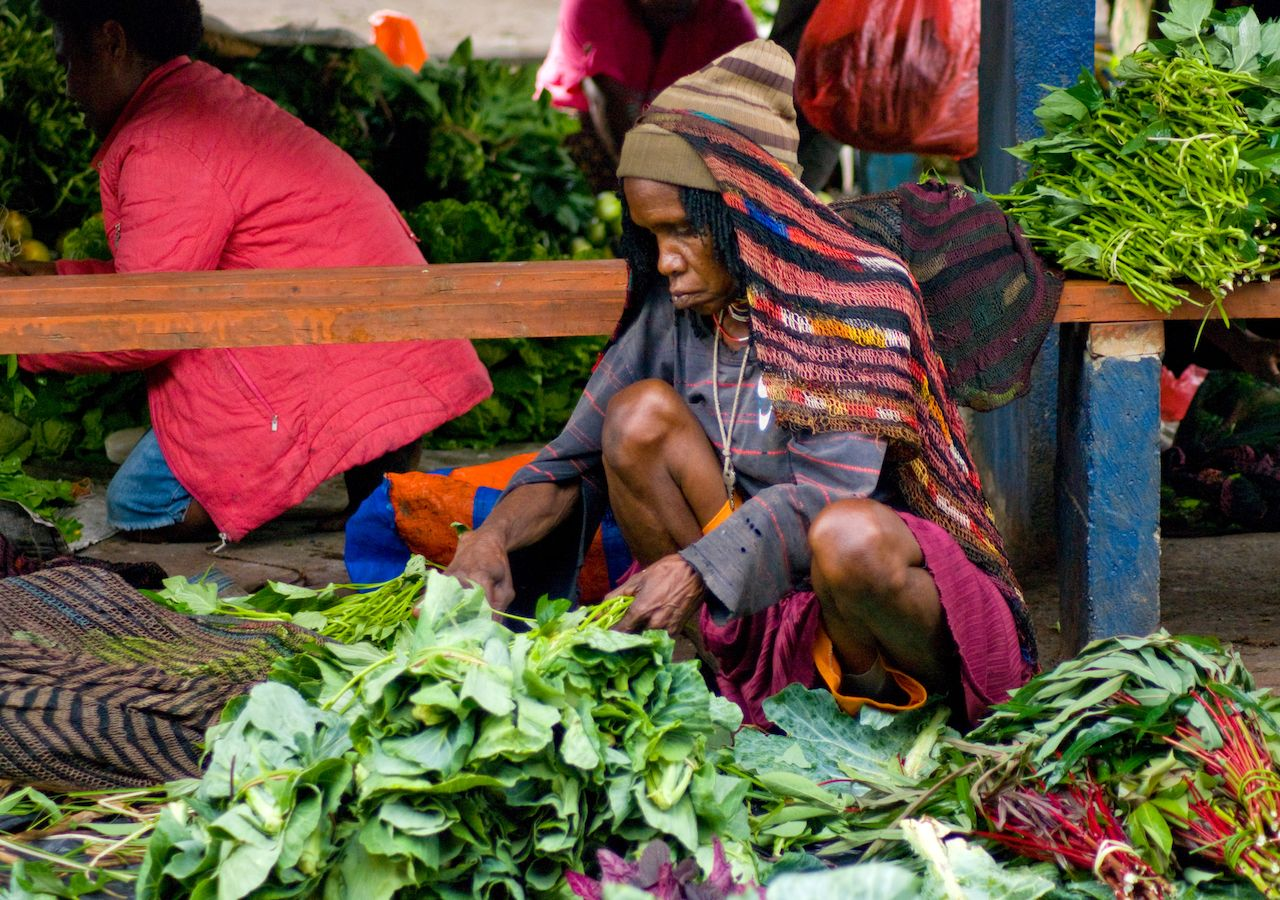 Vendor with vegetables at local market in New Guinea