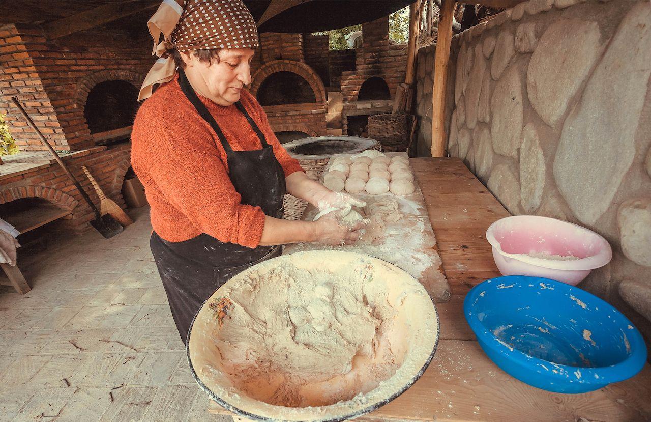 Woman baking homemade bread in Signagi, Georgia, Europe