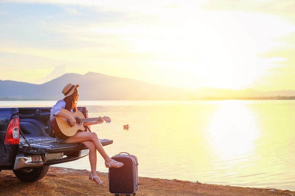 Woman playing guitar sunset