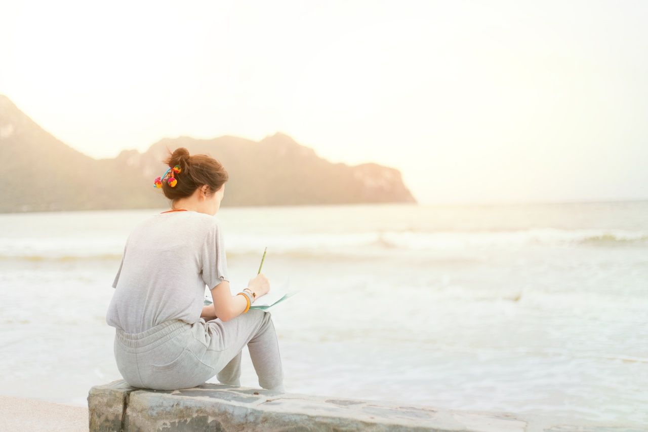 Woman writing at the beach