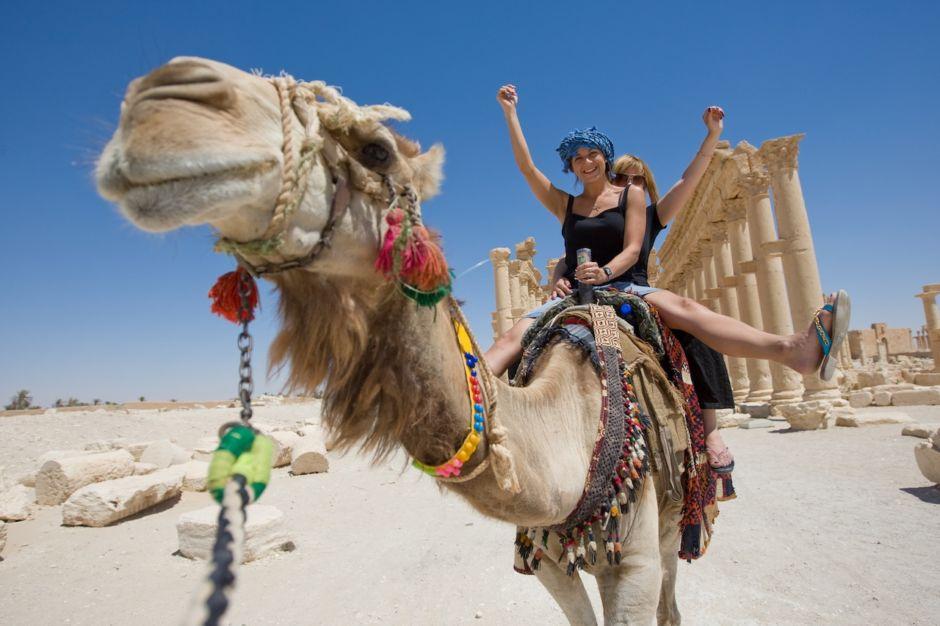 Women riding a camel in the Sahara desert
