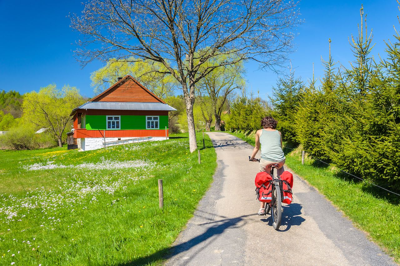 Young woman rides a bike on country road in spring time in the Banica village, Poland