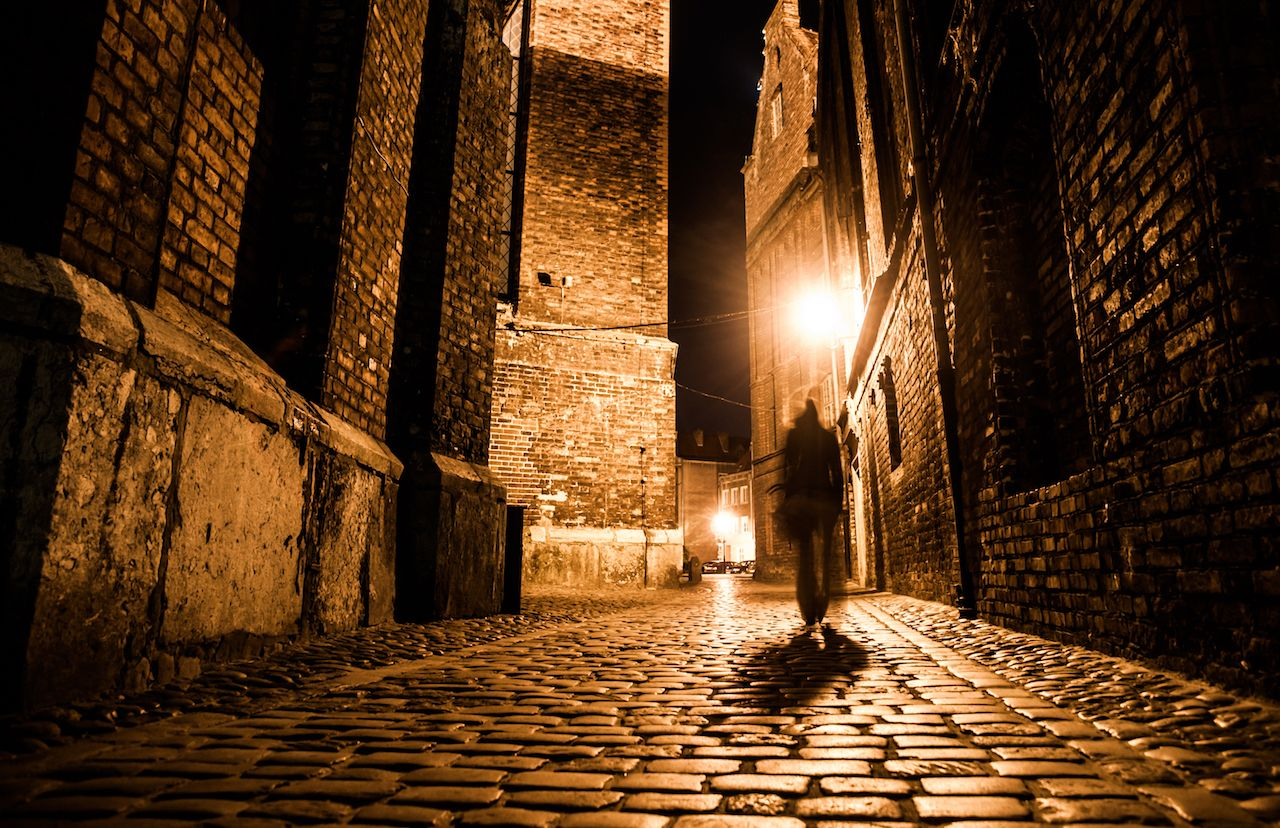 light reflections on cobblestones in old historical city by night