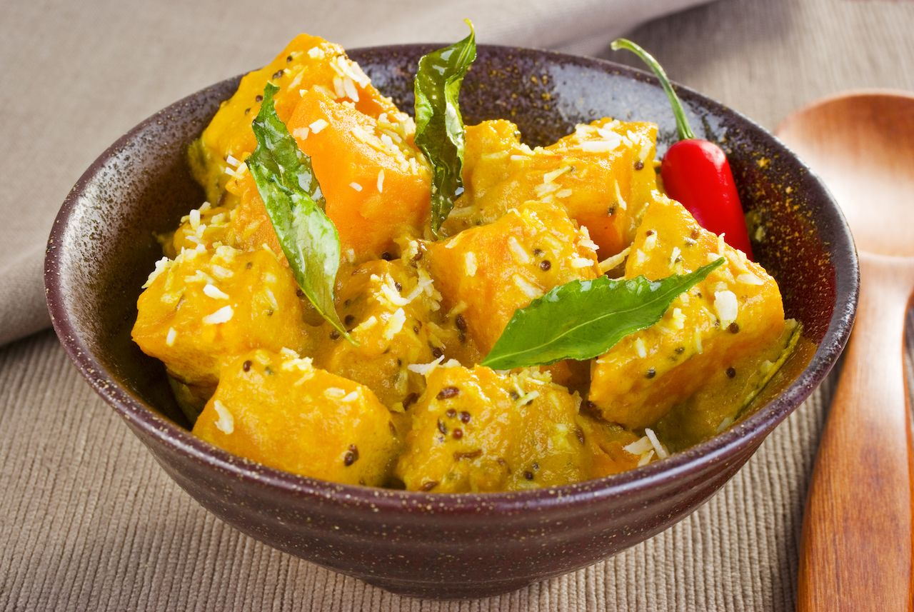 A bowl of chunky curry pumpkin, flavored with coconut, mustard seeds, cumin, chilli and curry leaves