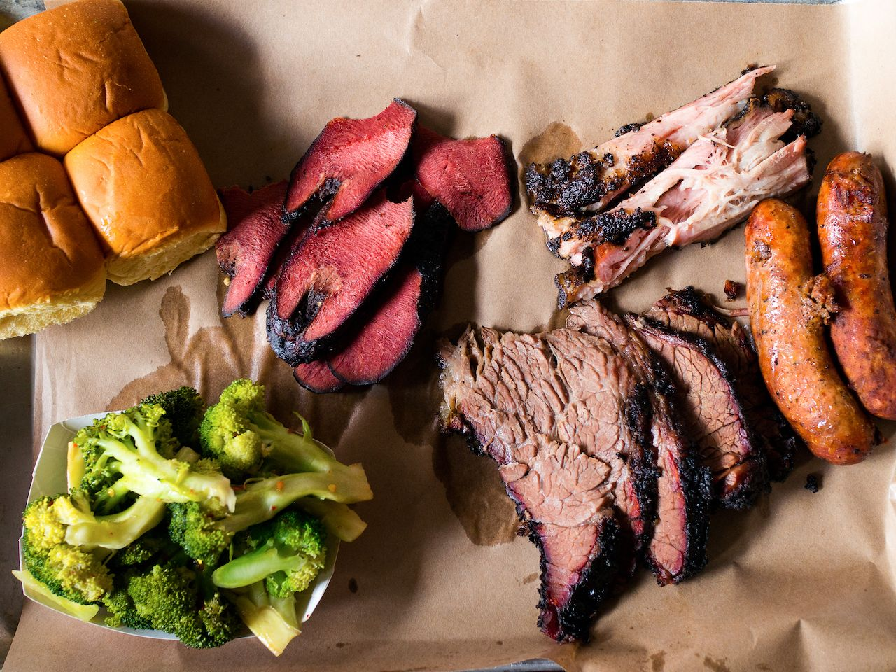 BBQ and smoked meats with broccoli and rolls