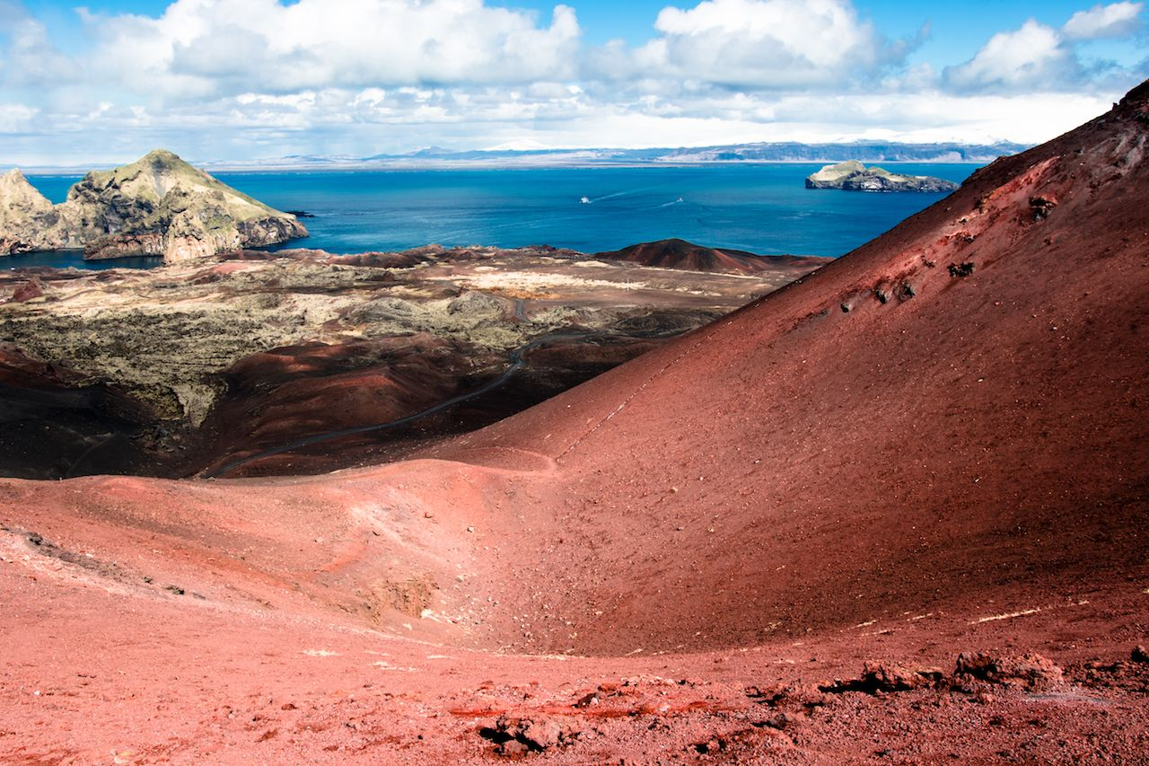 Beautiful colorful red lava stones and rocks on the top of volcano mountain in Westman islands Iceland
