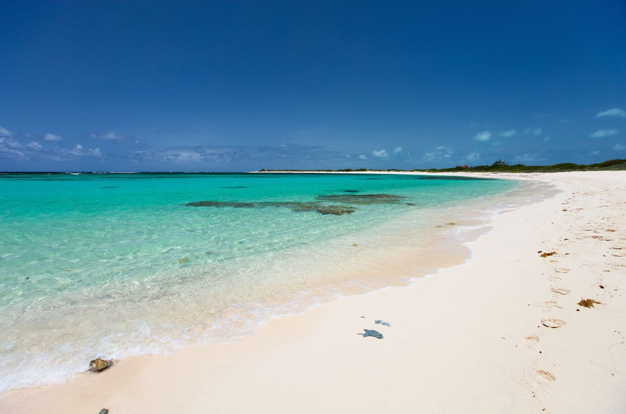 Beautiful tropical beach with palm trees, white sand, turquoise ocean water and blue sky at Anegada, British Virgin Islands