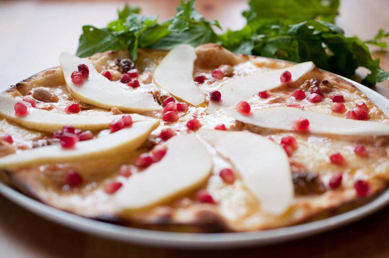 Turkish pizza topped with cheese and pomegranate seeds