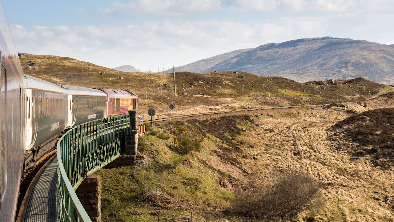 Caledonian Sleeper train crosses Rannoch Viaduct on the scenic West Highland Line railway in the Scottish Highlands