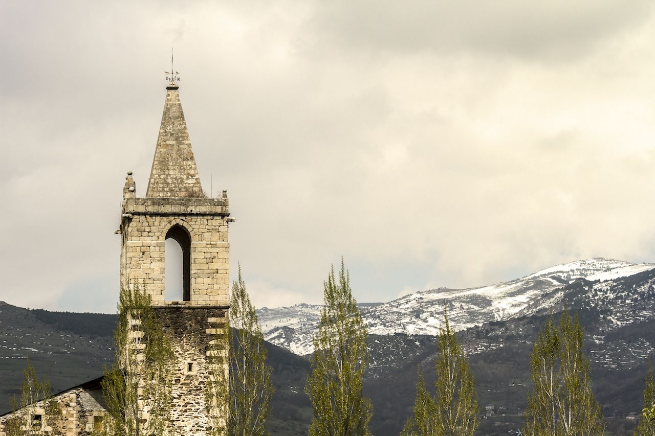 Church with the Pyrenees in the background in Llivia, Spain