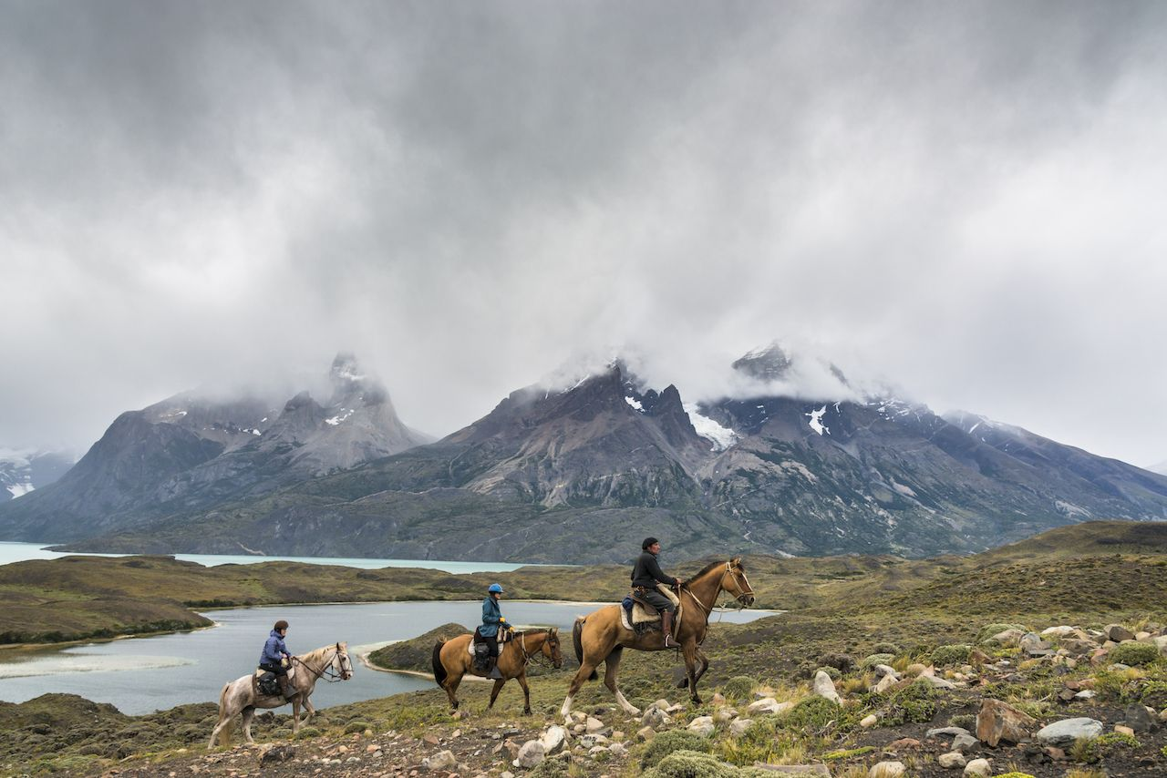 Gaucho with group of tourists riding horses Torres del Paine National Park