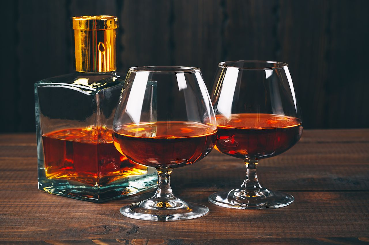 Glass of brandy or cognac on the wooden table