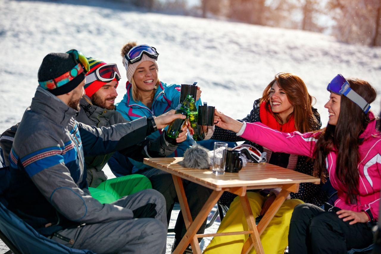 Group of happy friends cheering with drink after skiing day