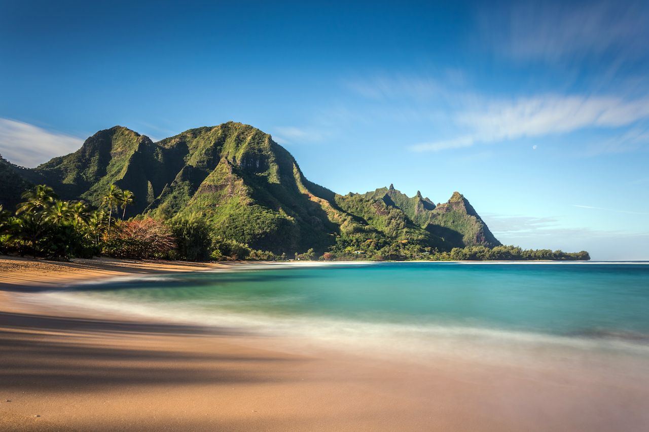 Hawaiian paradise with tall mountains, turquoise sea and white sand on Kauai