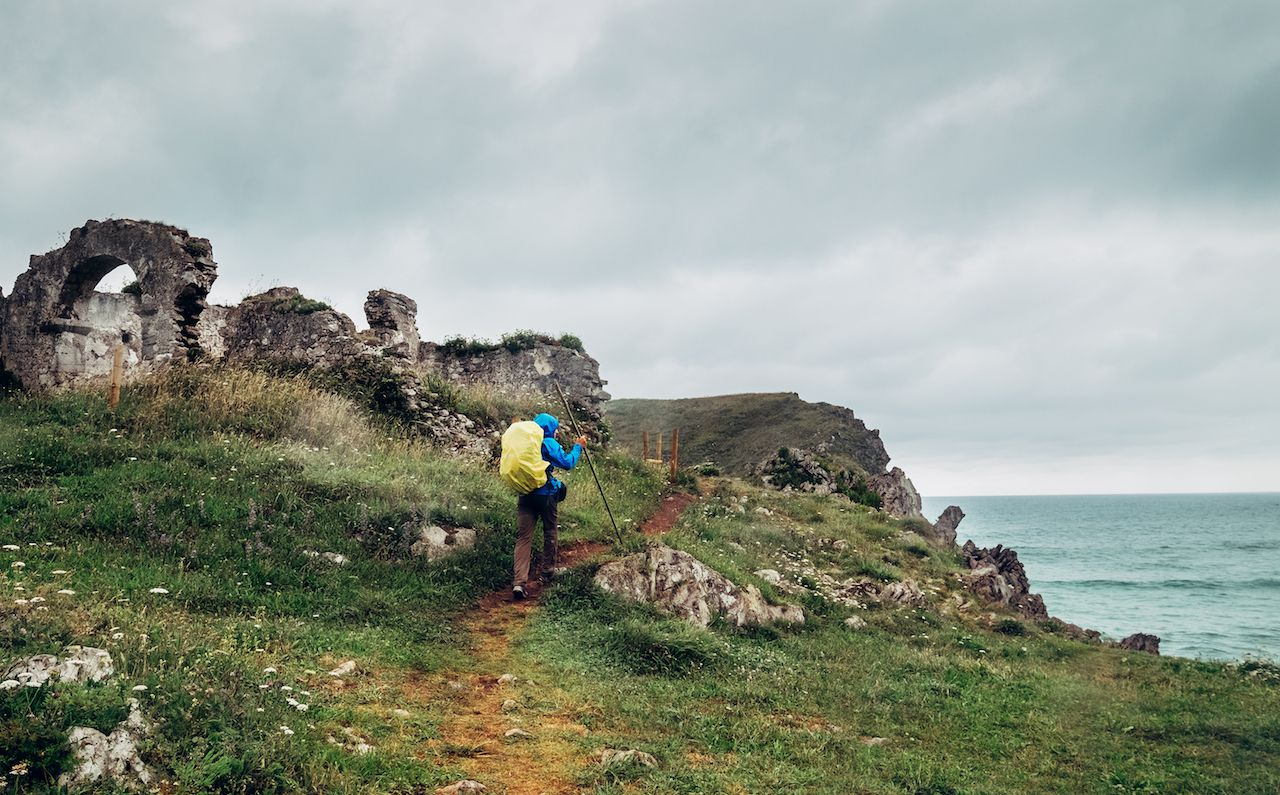 Hiker walking along the coast in northern Spain