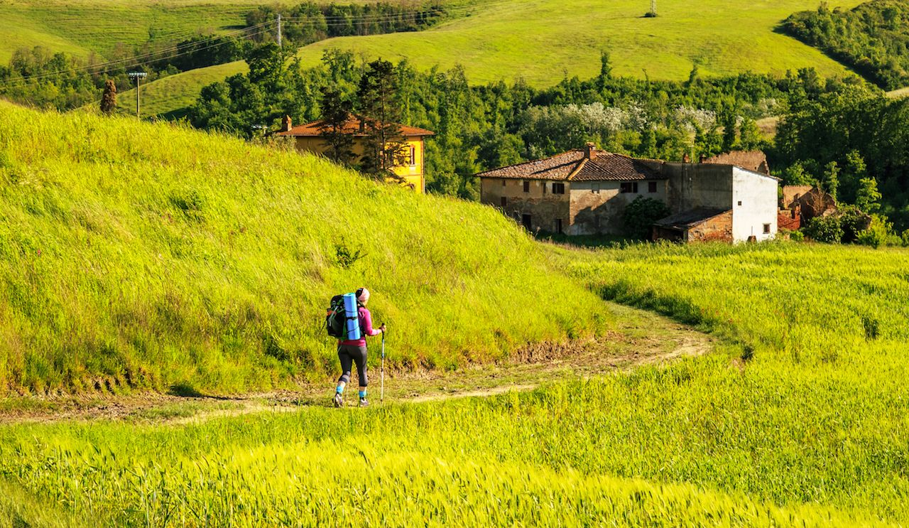 Hiker walking through the hills of Tuscany