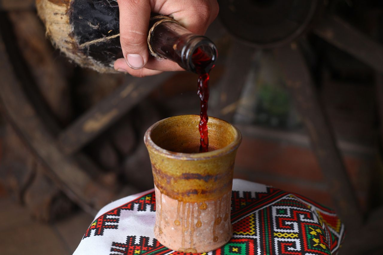Homemade Moldovan wine pouring from a traditional homemade bottle