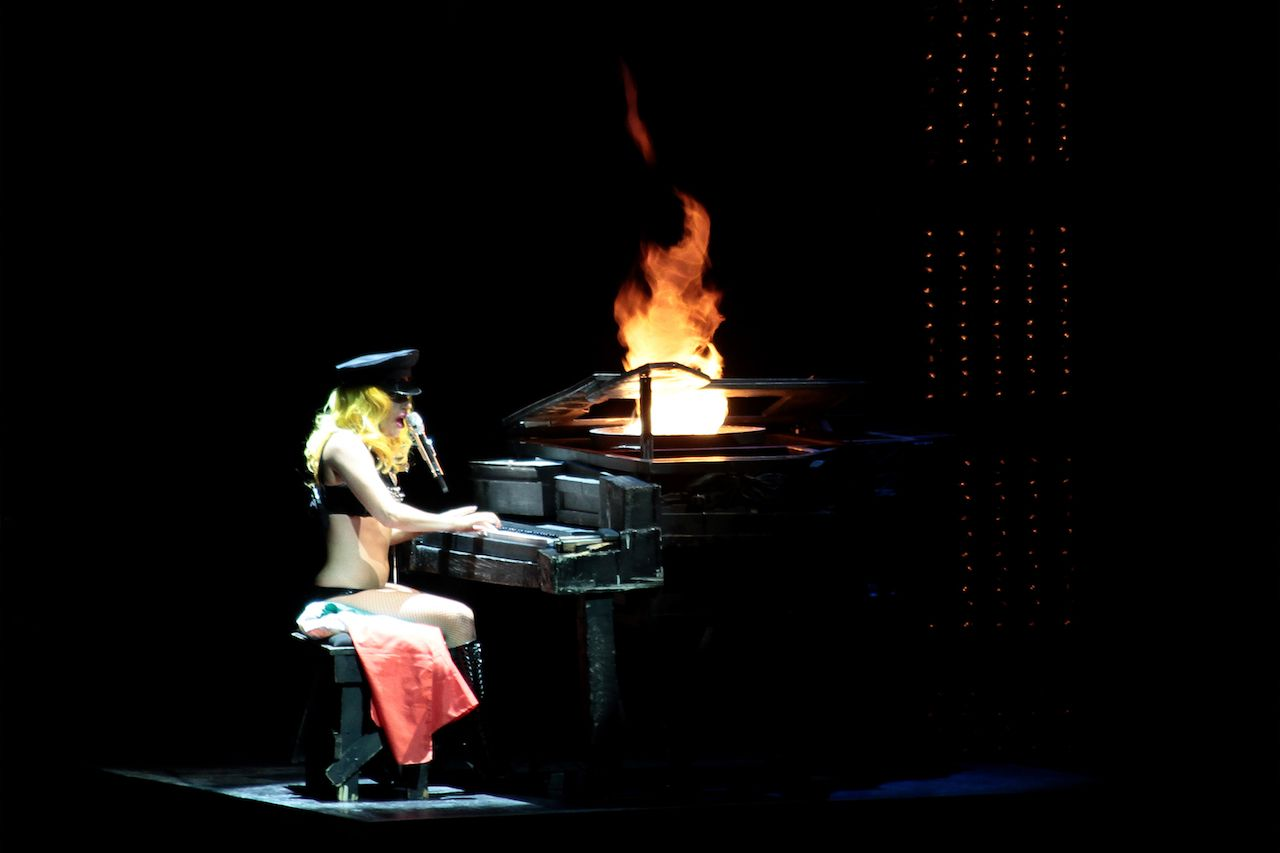 Lady Gaga performing with a flaming piano