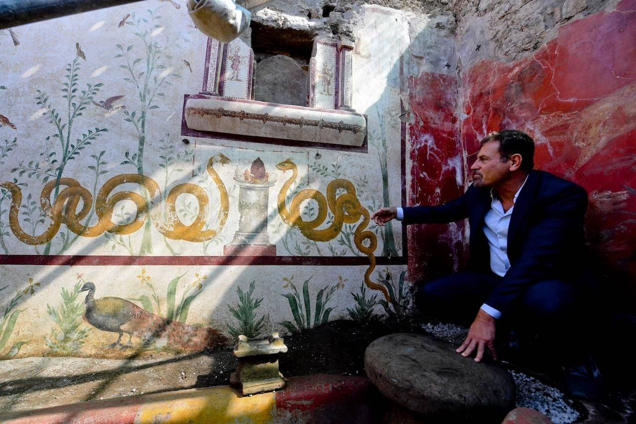Man squatting next to a shrine in the ruins of Pompeii, Italy