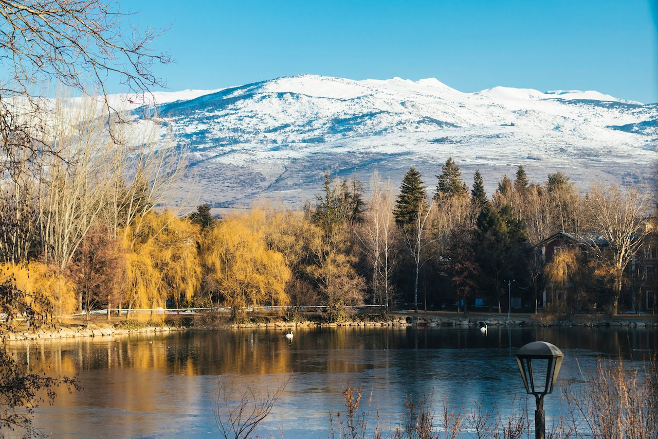 Puigcerda lake in winter with snowy mountain peak and yellow trees reflected