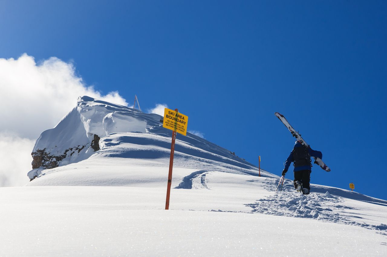 Skier hiking along a cornice in fresh snow