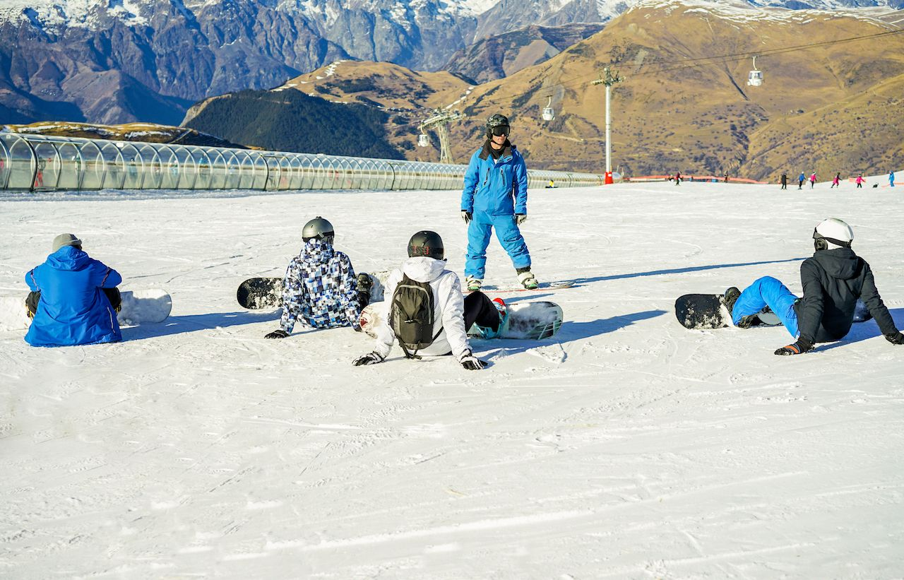 Snowboarder instructor teaching apprentice learners