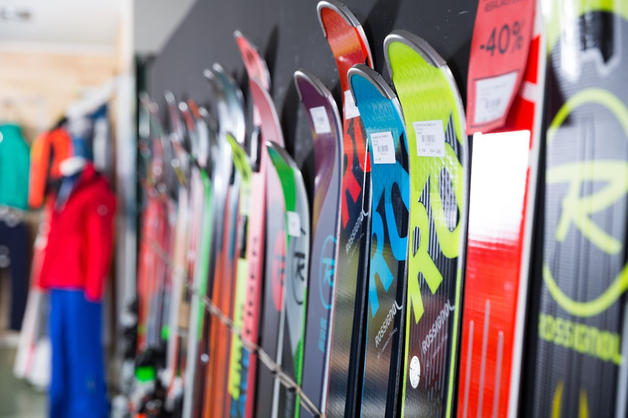 Sport goods store interior with large choice of modern skis