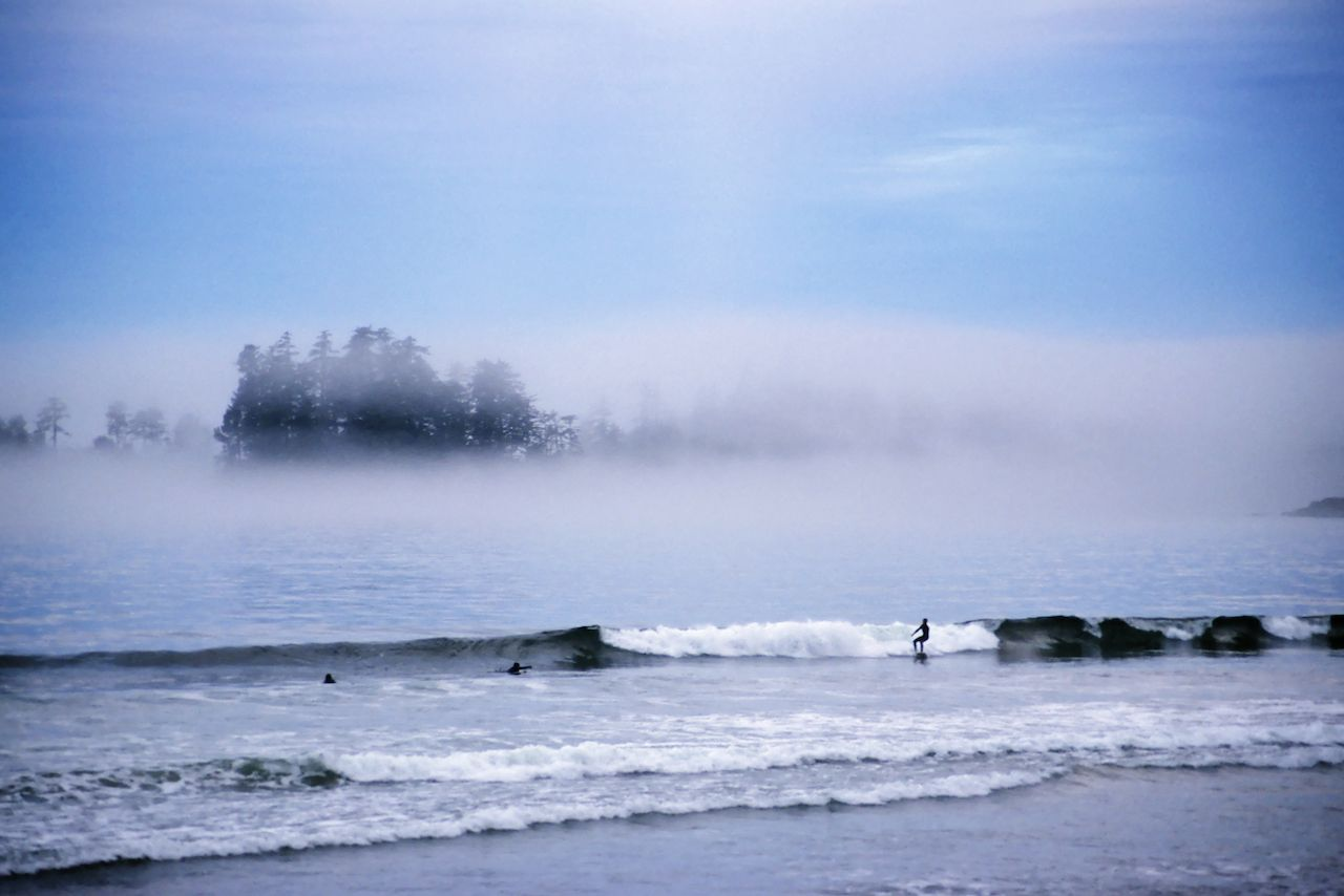 Surfers in Tofino with mist around it
