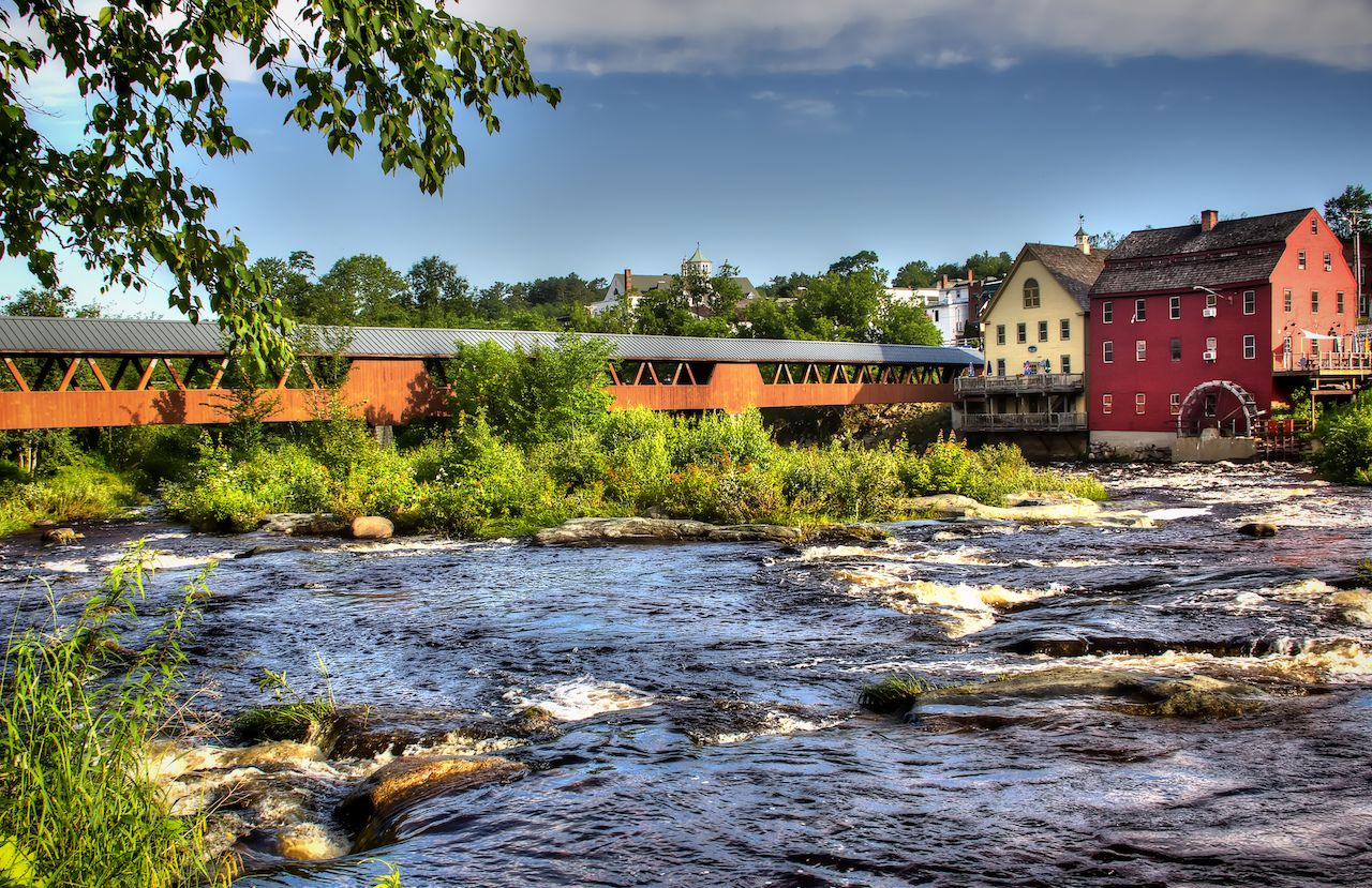 The River Walk Covered Bridge with the Grist mill on the Ammnosuoc River in Littleton New Hampshire