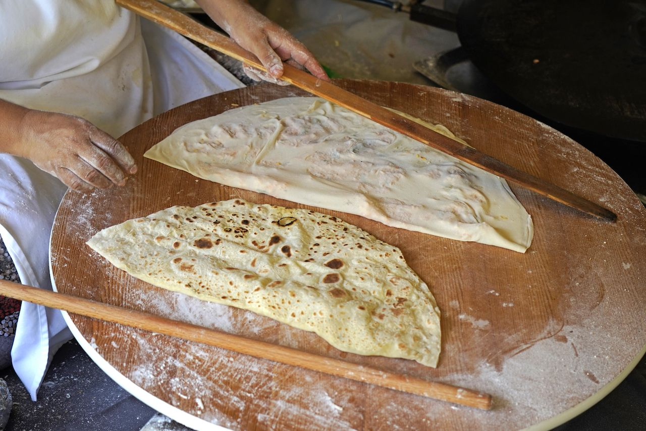 Traditional Turkish stuffed flatbread called Gozleme being made