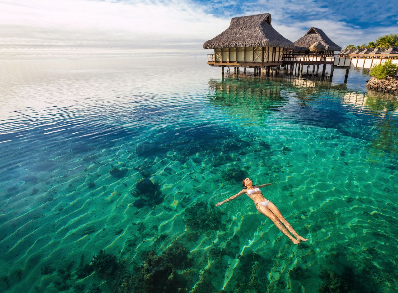 Woman in white bikini swimming in lagoon coral at the resort, Moorea, Tahiti