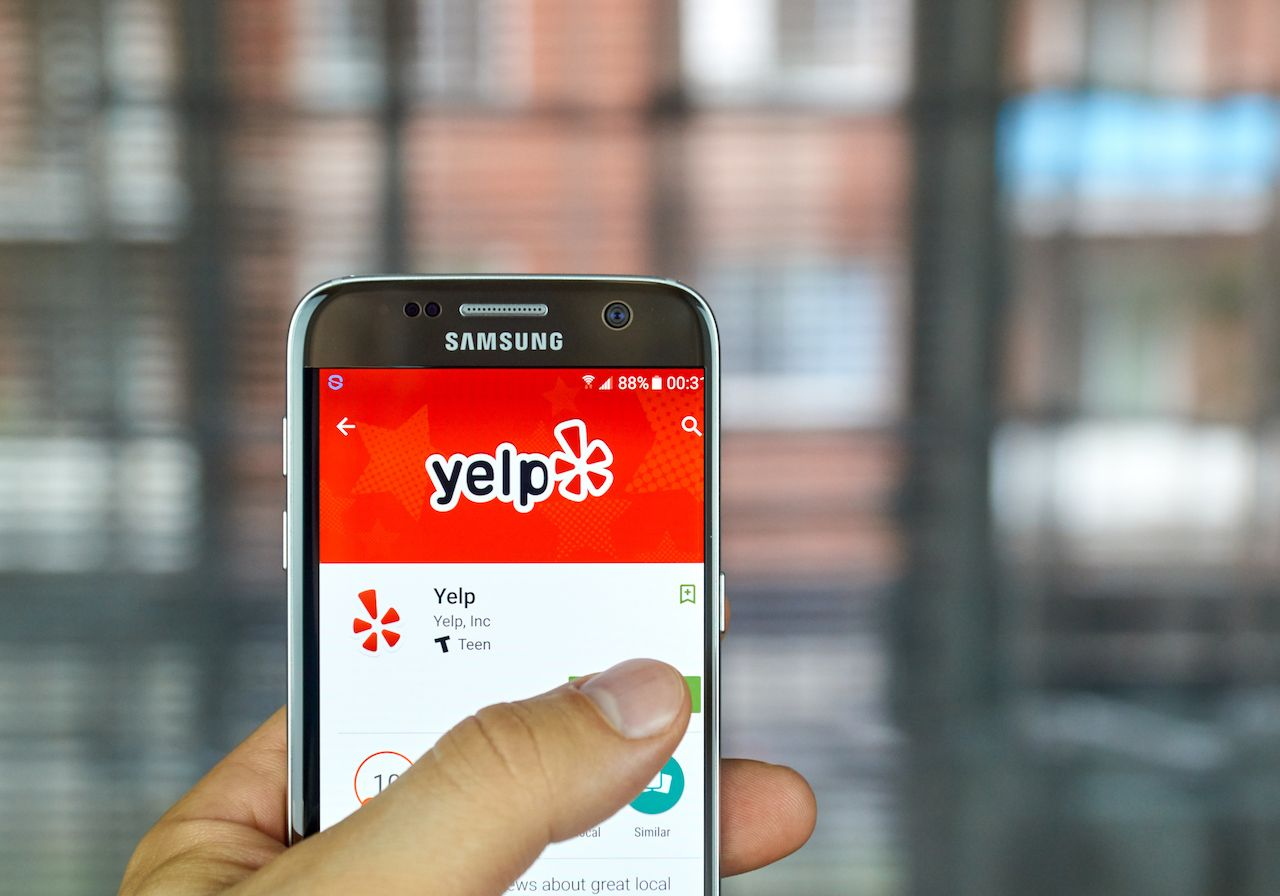 Yelp mobile app on screen Samsung S7 in hand