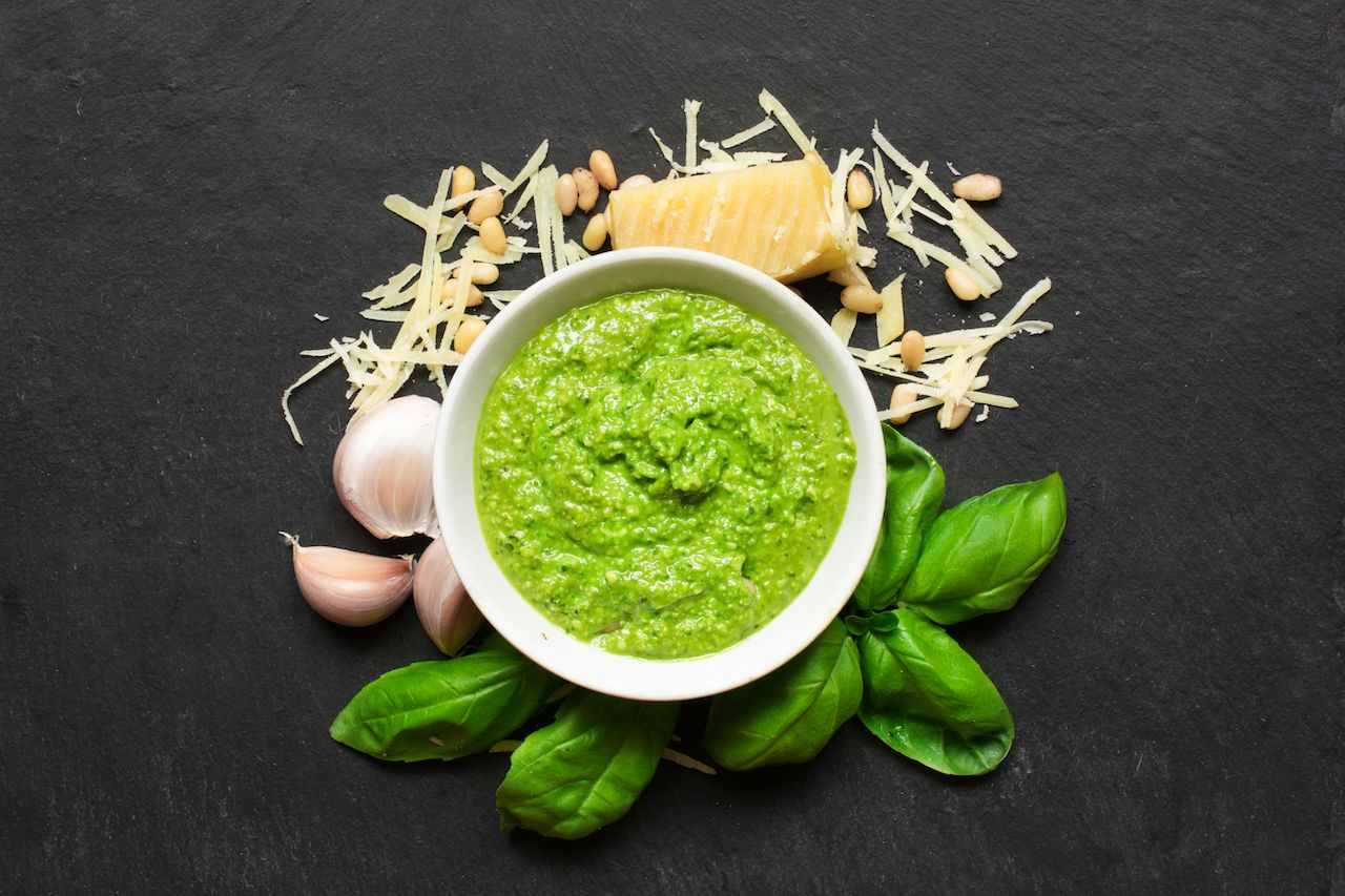 bowl of pesto surrounded by parmesan, pine nuts, garlic, and basil