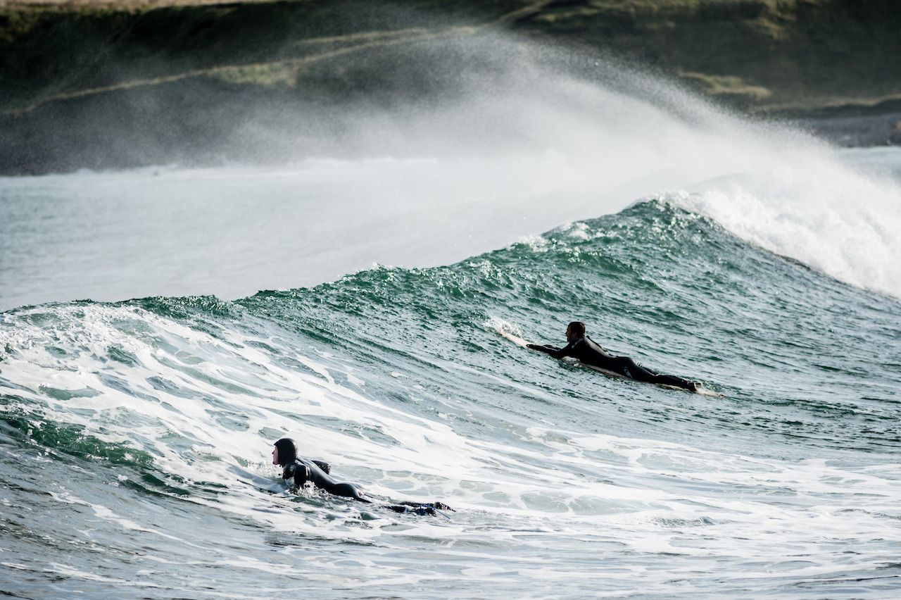 surfers in wetsuits riding waves