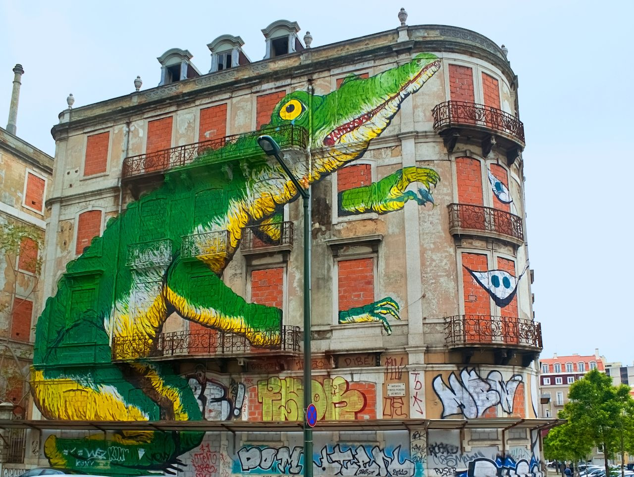 Building with a green lizard on it street art in Lisbon, Portugal